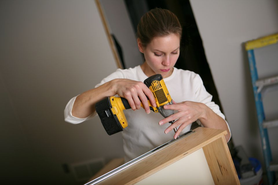 A woman using a drill to build furniture