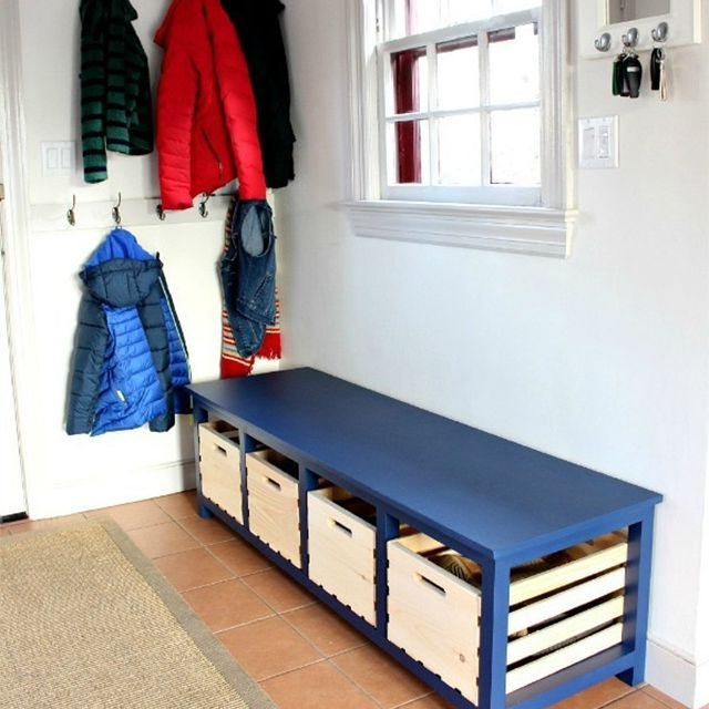 A blue bench by a coat rack
