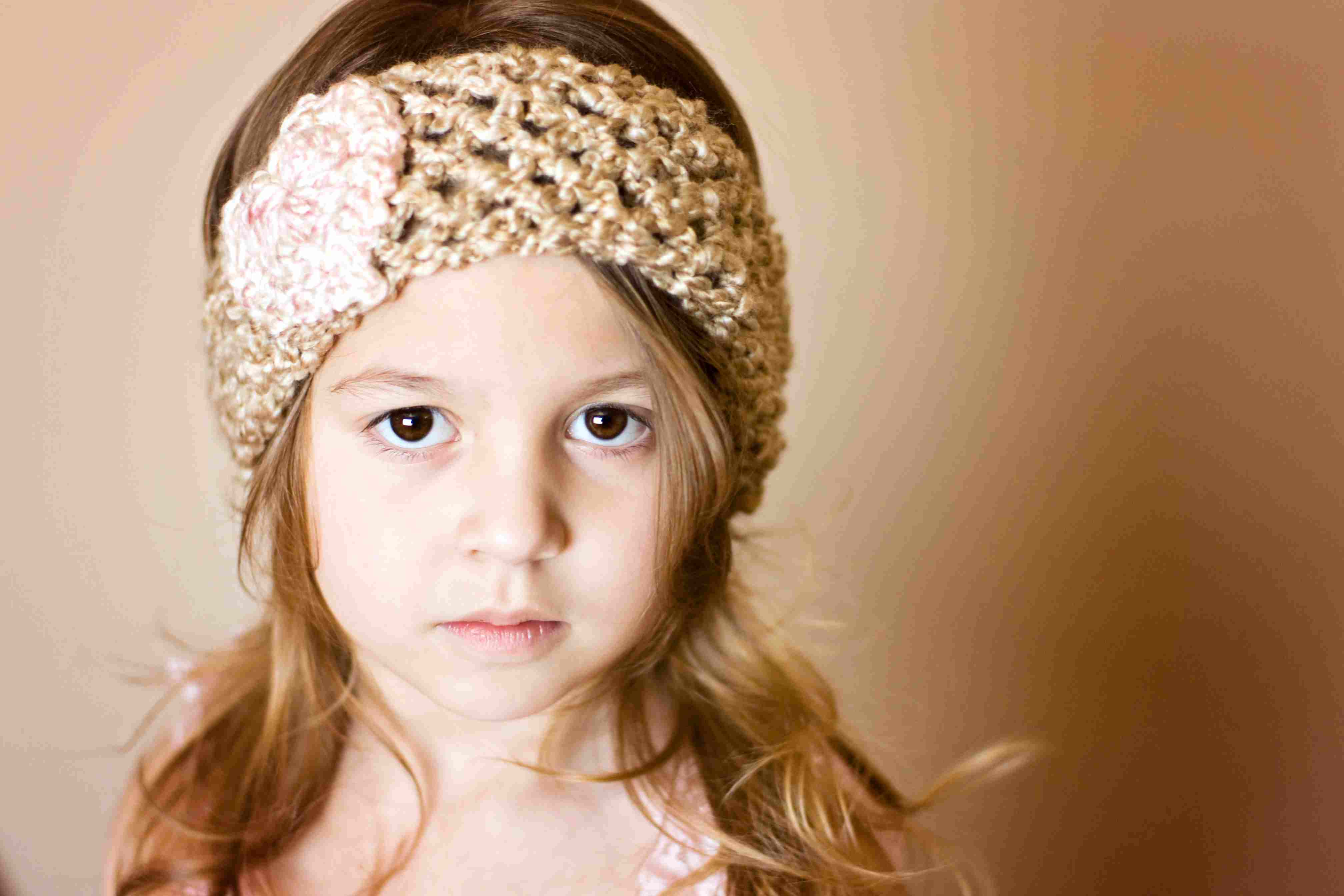 Handmade crocheted earwarmers worn by a young girl