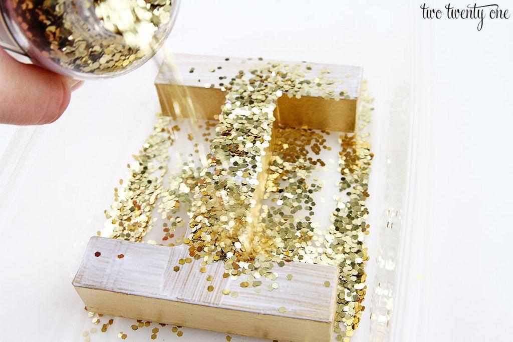 "A hand pouring gold glitter flecks onto a paper mache letter ""I"""