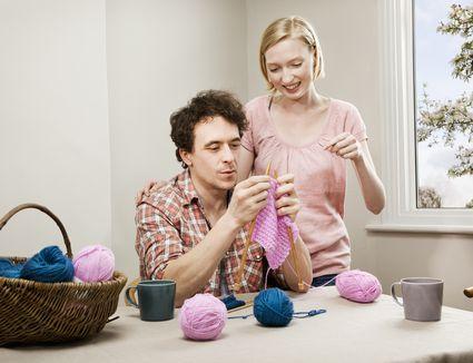 A woman teaches a man to knit