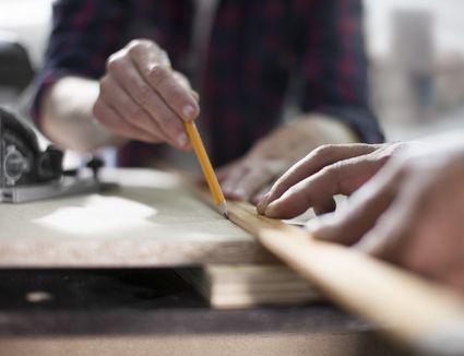 hands measuring a wood board