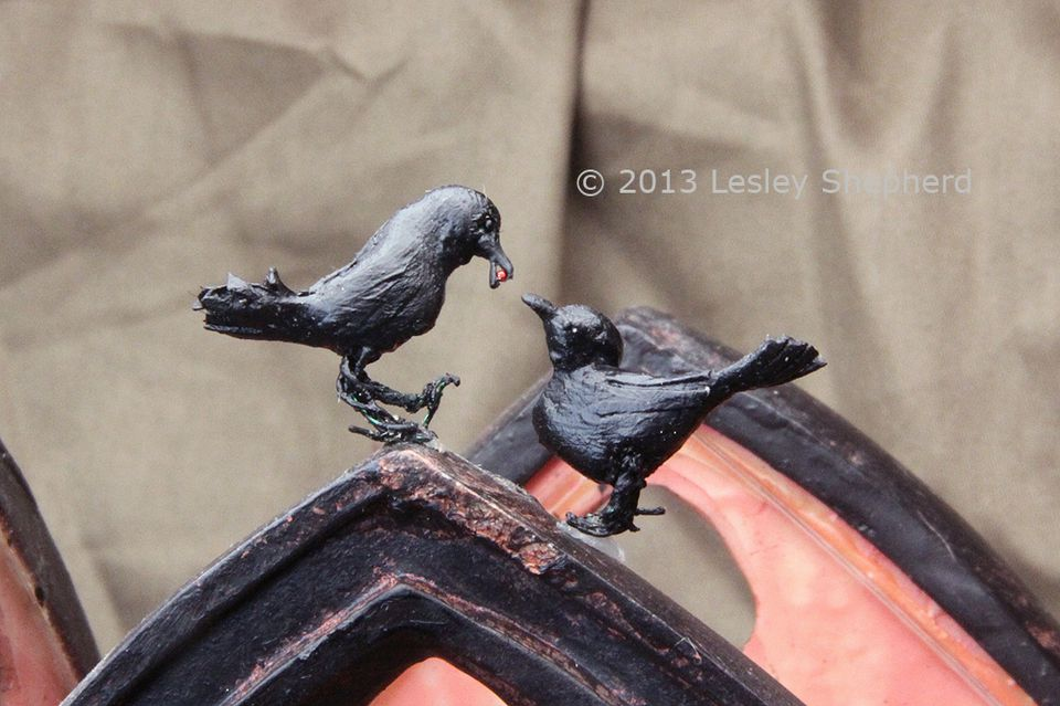 Two miniature crows in dollhouse scale posed on top of a gothic candle surround.