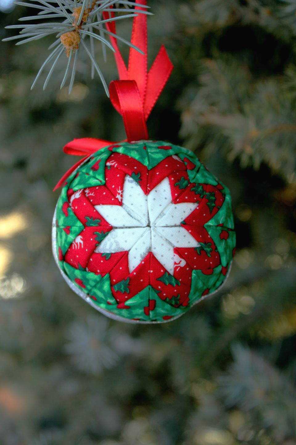 A quilted ornament hanging in a Christmas tree