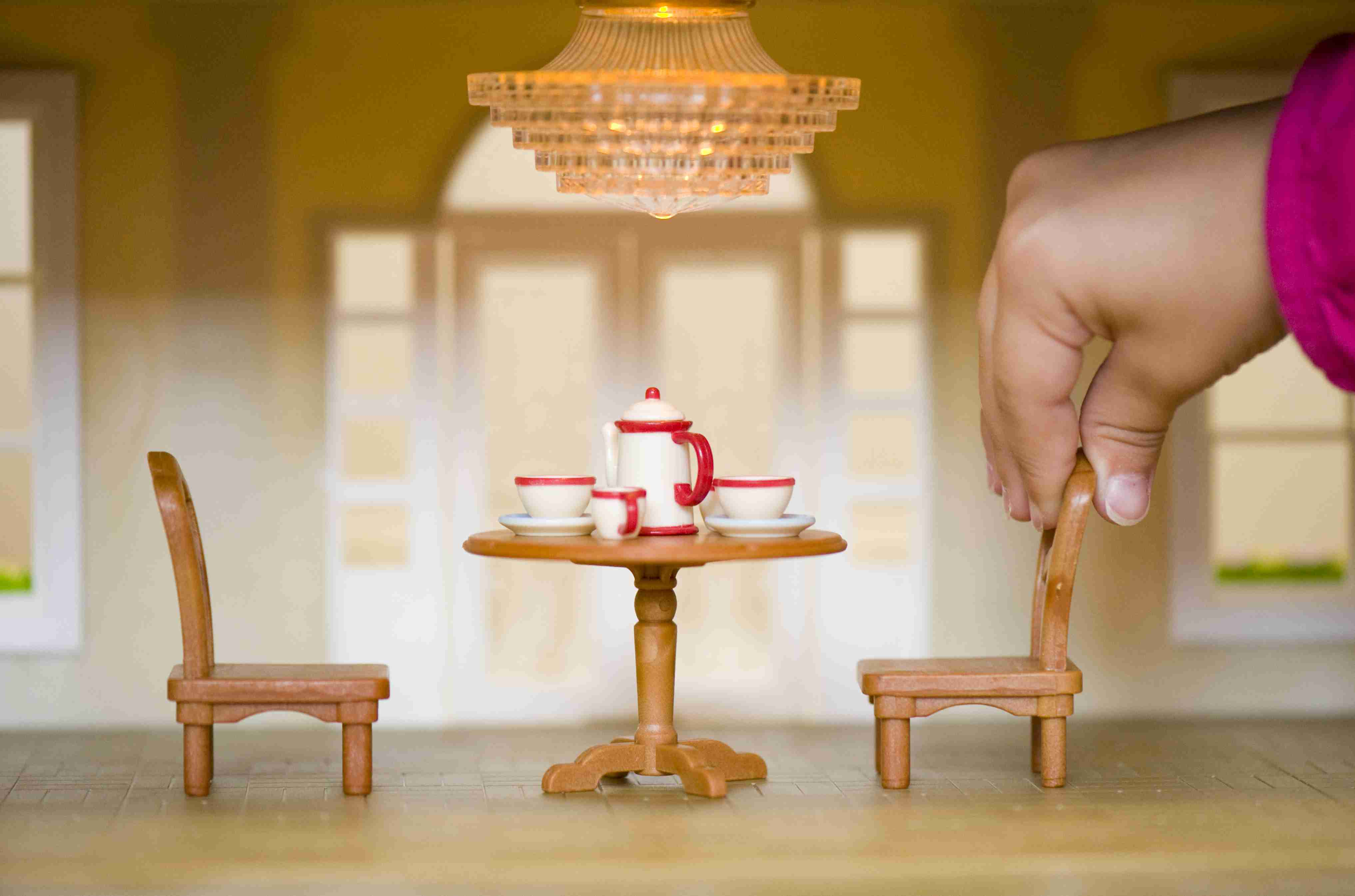 Child's hand arranging chair and table with tea set in a dollhouse.