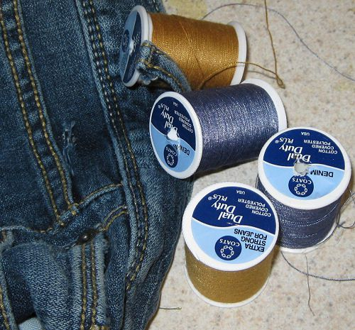 Spools of thread beside denim