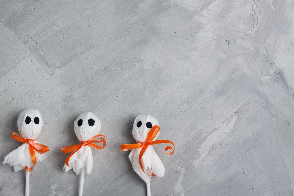 Three halloween lollipop ghosts on gray concrete background
