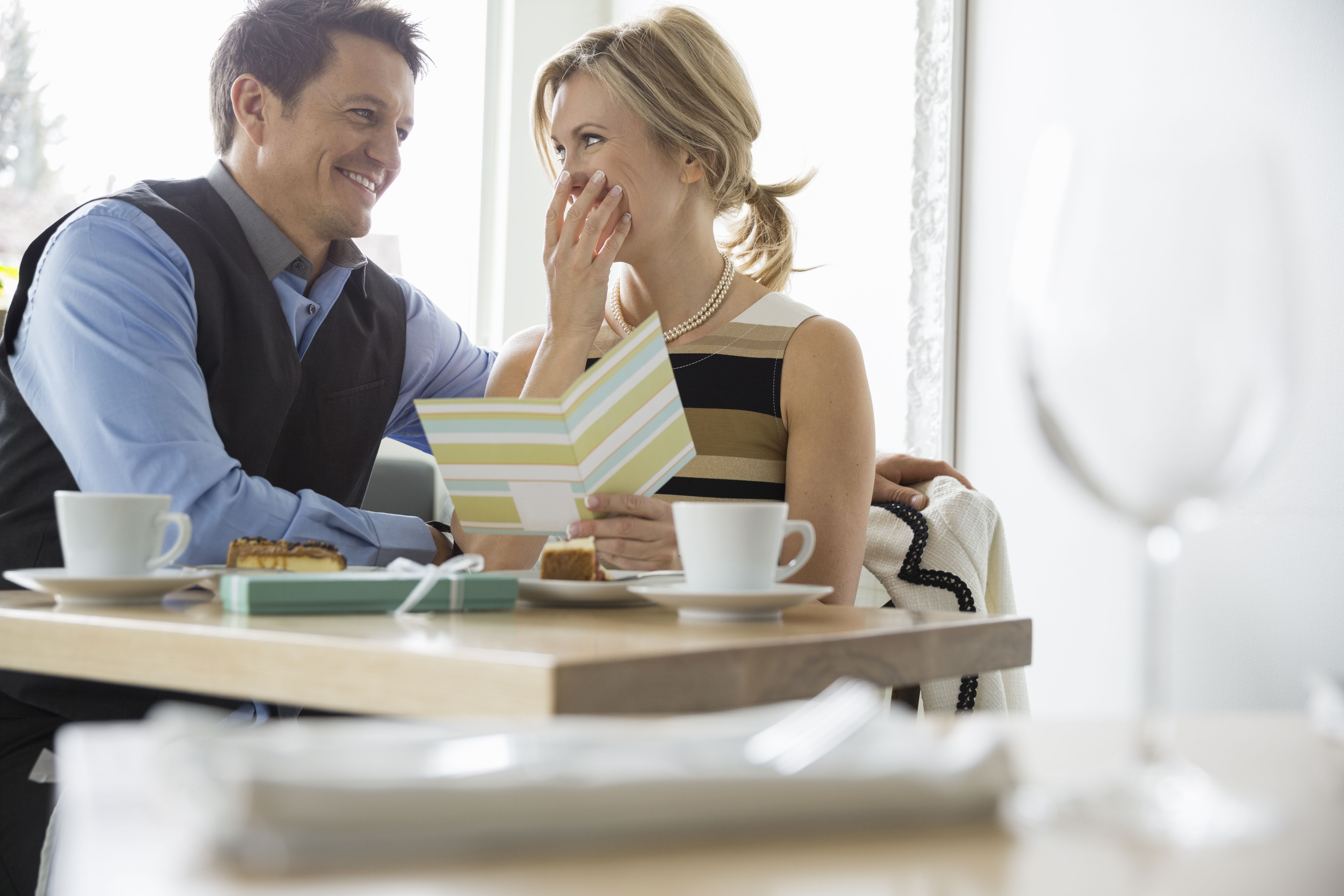 Man surprising woman with card