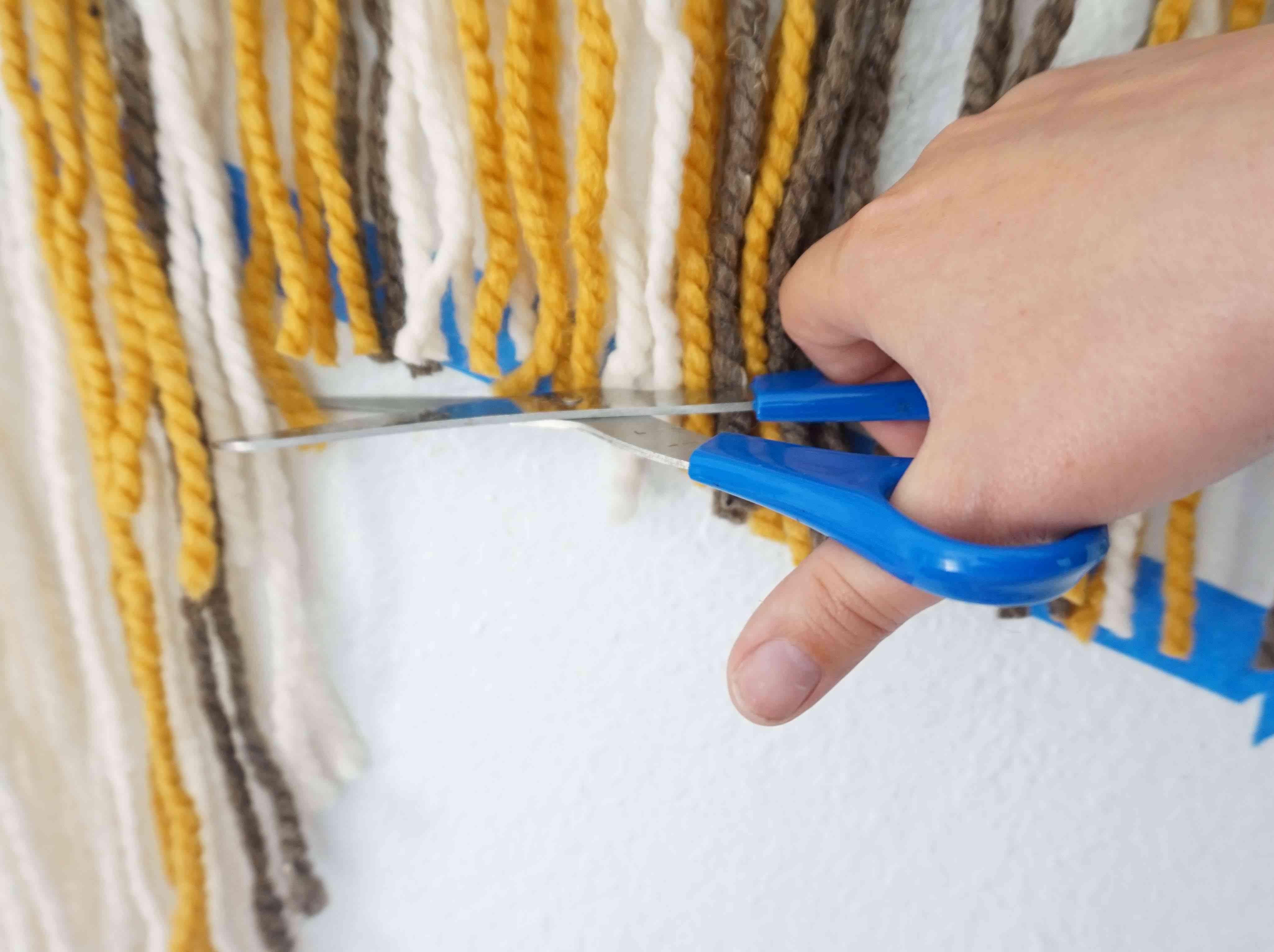 Cutting yarn in wall hanging.