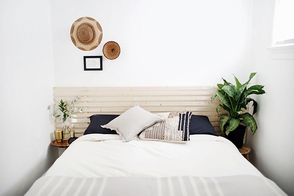 A slat wooden headboard above a bed