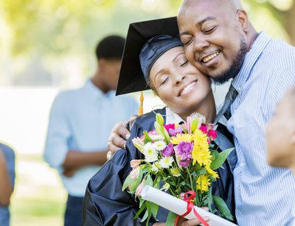 A happy garduate receives a bouqeut of flowers from her loving family