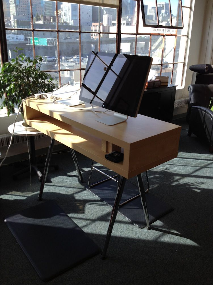 A standing desk made from an IKEA product next to windows.