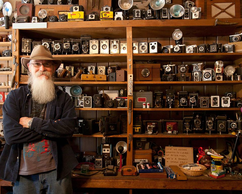Man with beard standing in front of a shelf of old cameras