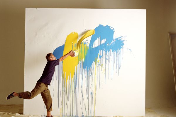 Artist throwing paint across the canvas
