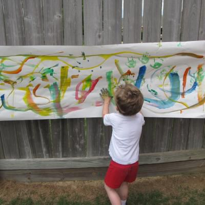 Child finger painting against fence
