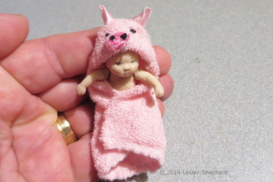 Dollhouse baby in a hooded towel with a pig face.
