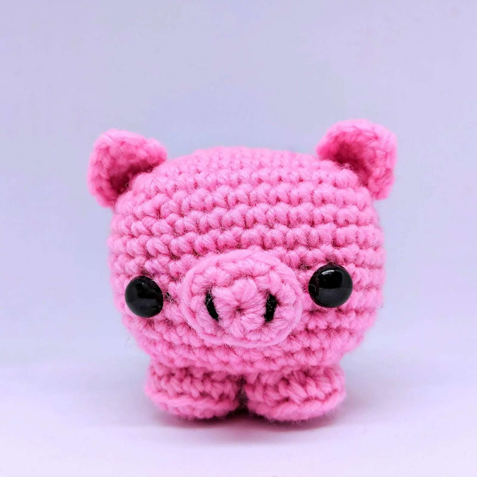 Pink crochet pig with a white background.