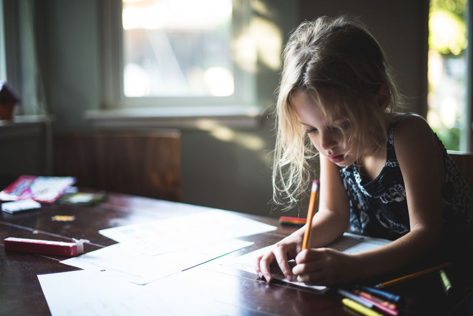 Girl Writing with Pencil at Table