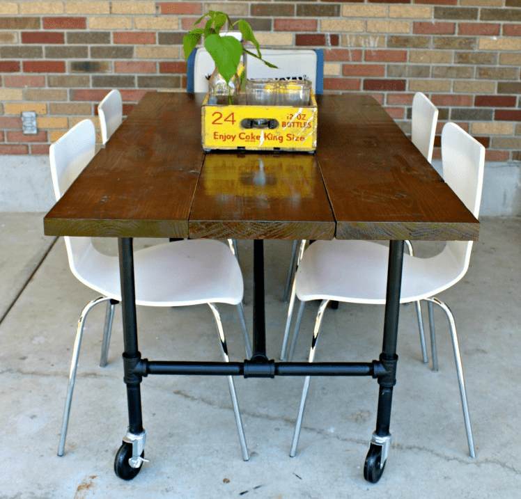 A Wooden Table With Plumbing Pipes as Legs