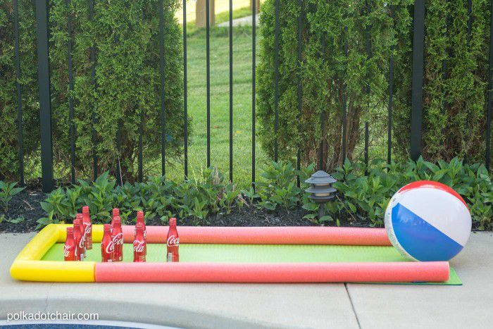 DIY outdoor bowling game with pool noodle lane, beach ball, and plastic Coke bottles.