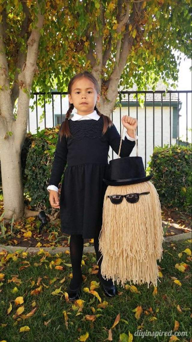 """Girl modeling a """"Cousin It"""" Trick or Treat Pail"""