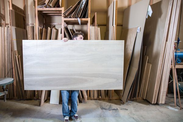 A man moving a large piece of wood in a workshop