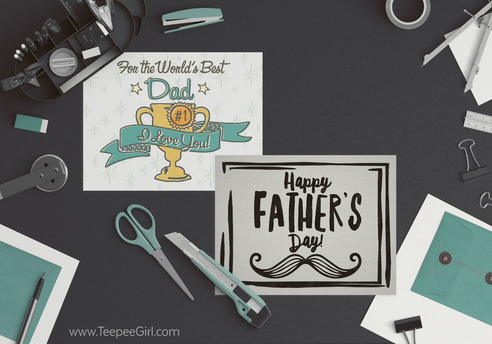 Two Father's Day cards laying on a table with craft supplies