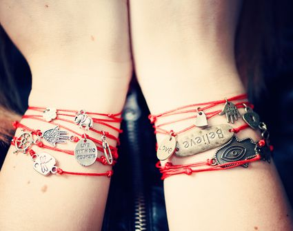 woman wearing string charm bracelets