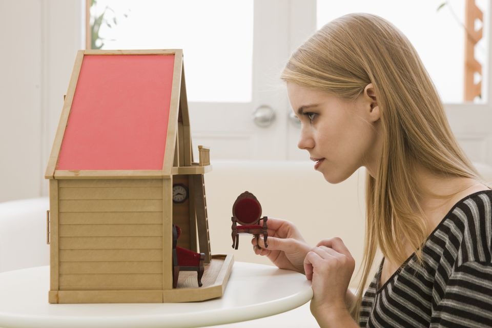 Young Woman Looking at Dollhouse