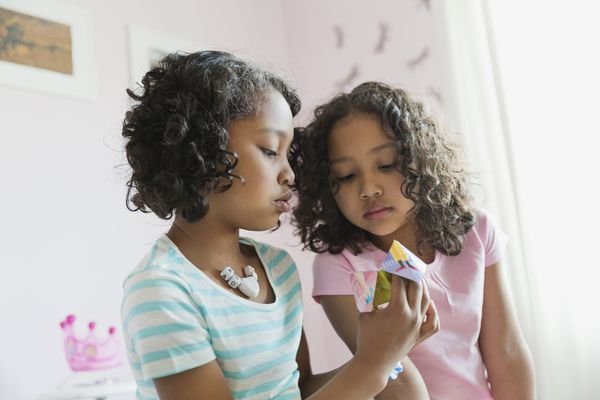 Young girls playing paper fortune teller game