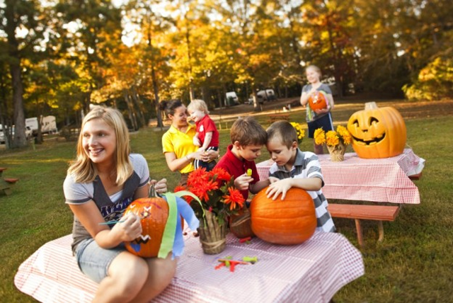 Picture of kids carving pumpkins outside
