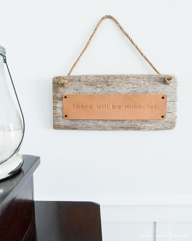 Driftwood sign with a leather plate that reads: There will be miracles.