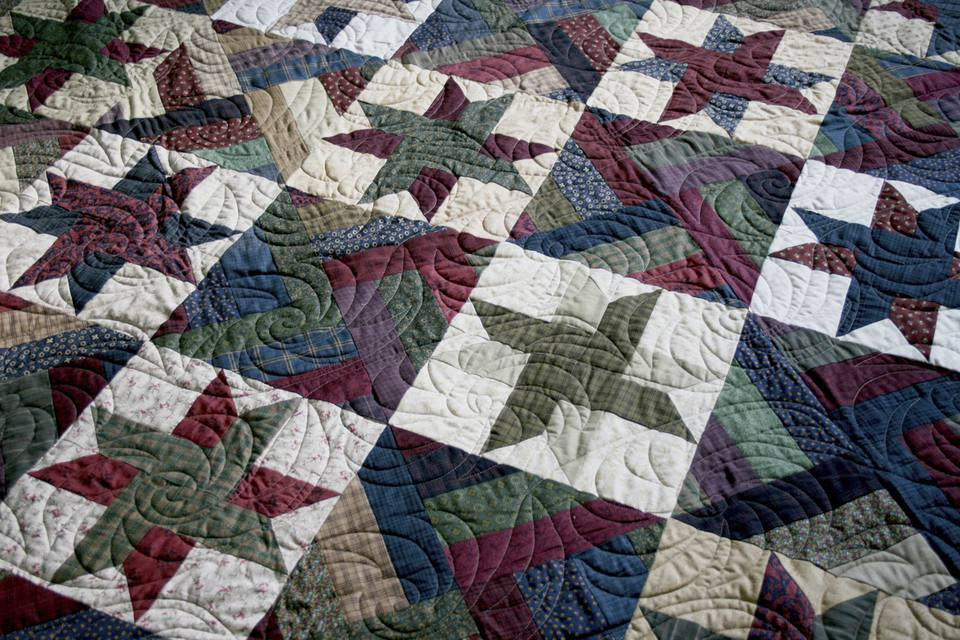 Patchwork quilt lying on the bed.