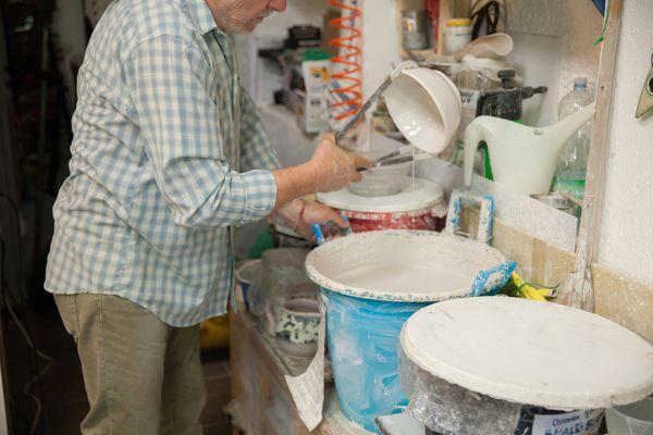 man glazing pottery in studio