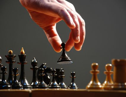 Hand moving the pieces of a chess board, close-up