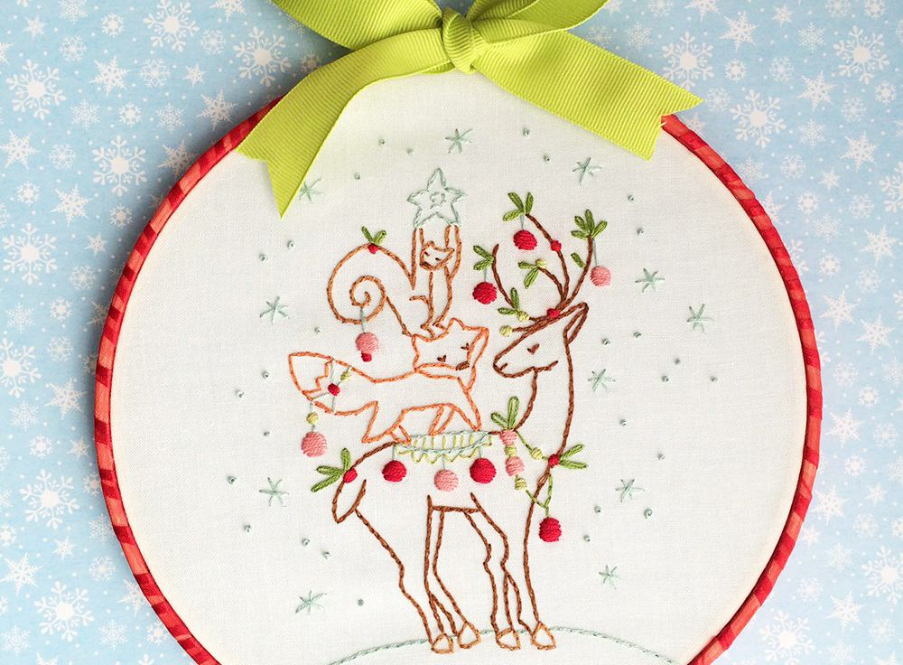 Embroidered reindeer, fox, and squirrel standing on top of each other, and placed in a red embroidery hoop with yellow bow.