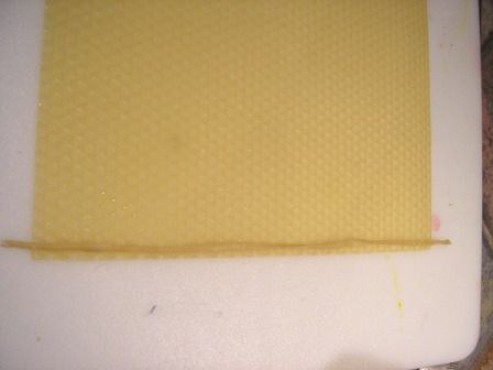 Candle wick next to a sheet of beeswax