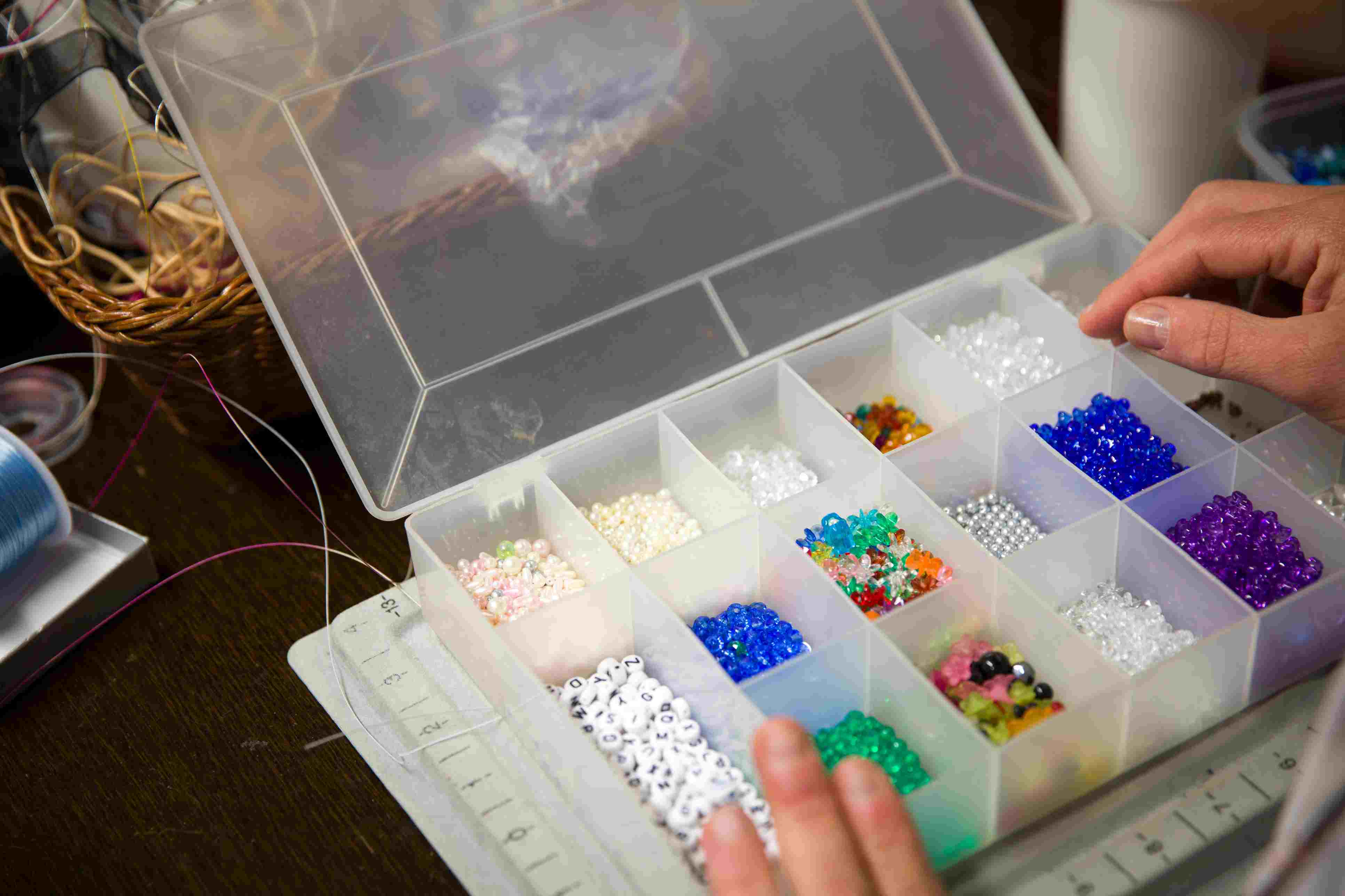 Cropped Image of Tailor Hand Holding Box of Beads