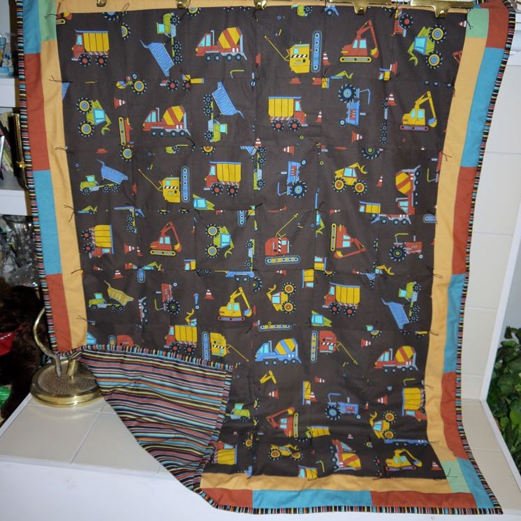 Tonka toys quilt hanging on a wall.