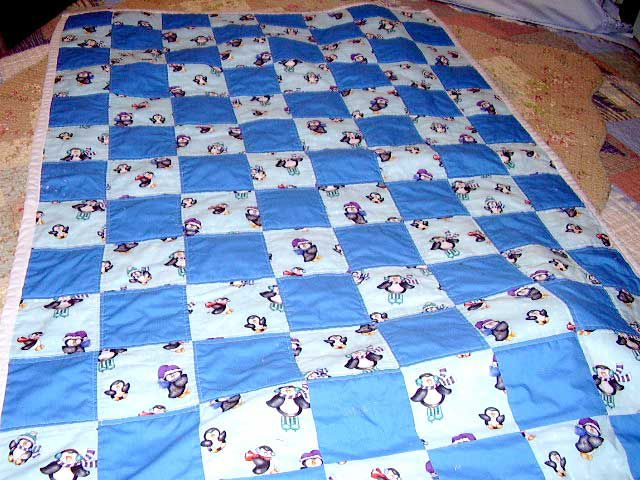Blue baby quilt with penguins.