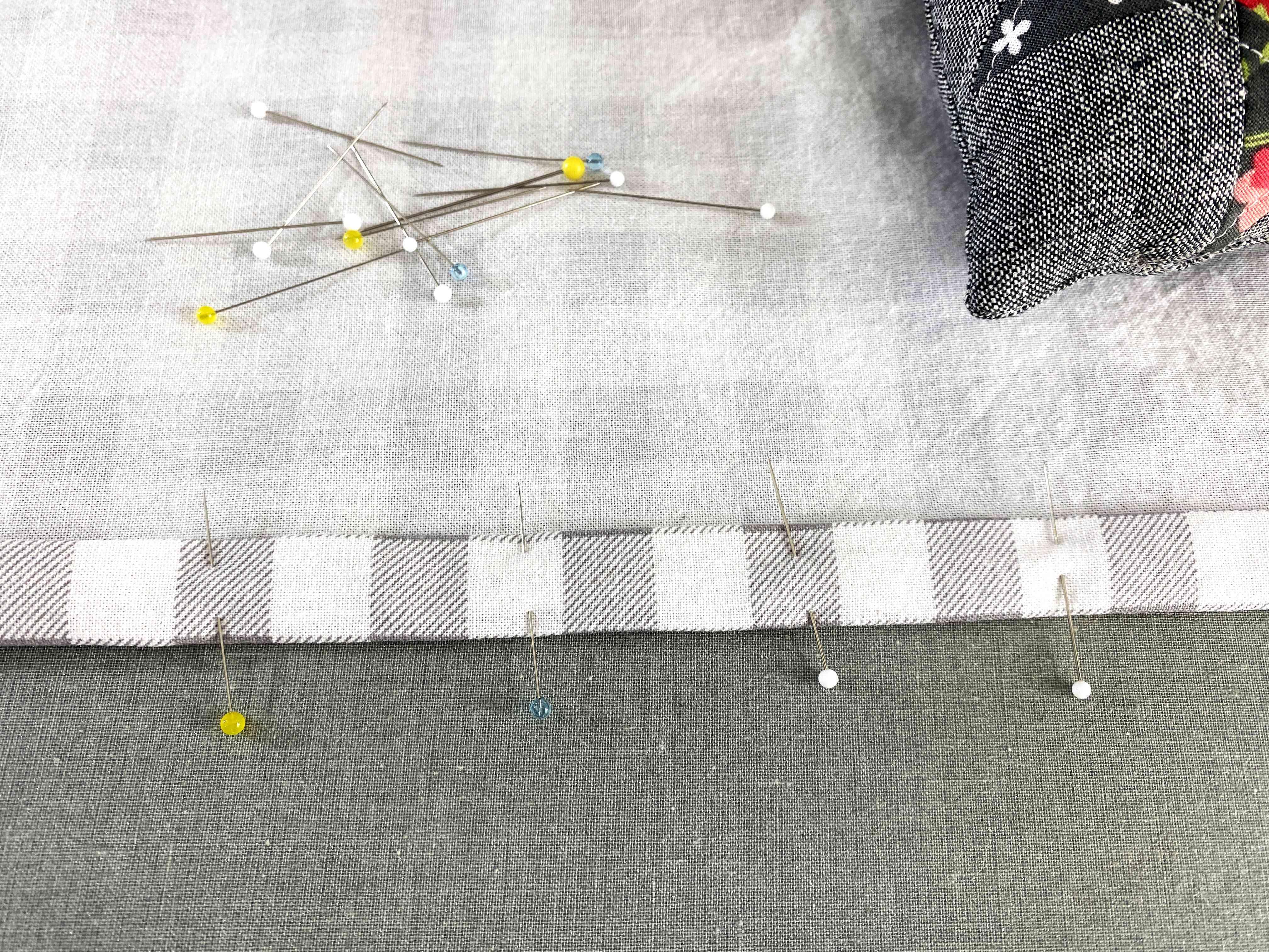 Pins hemming the edge of fabric