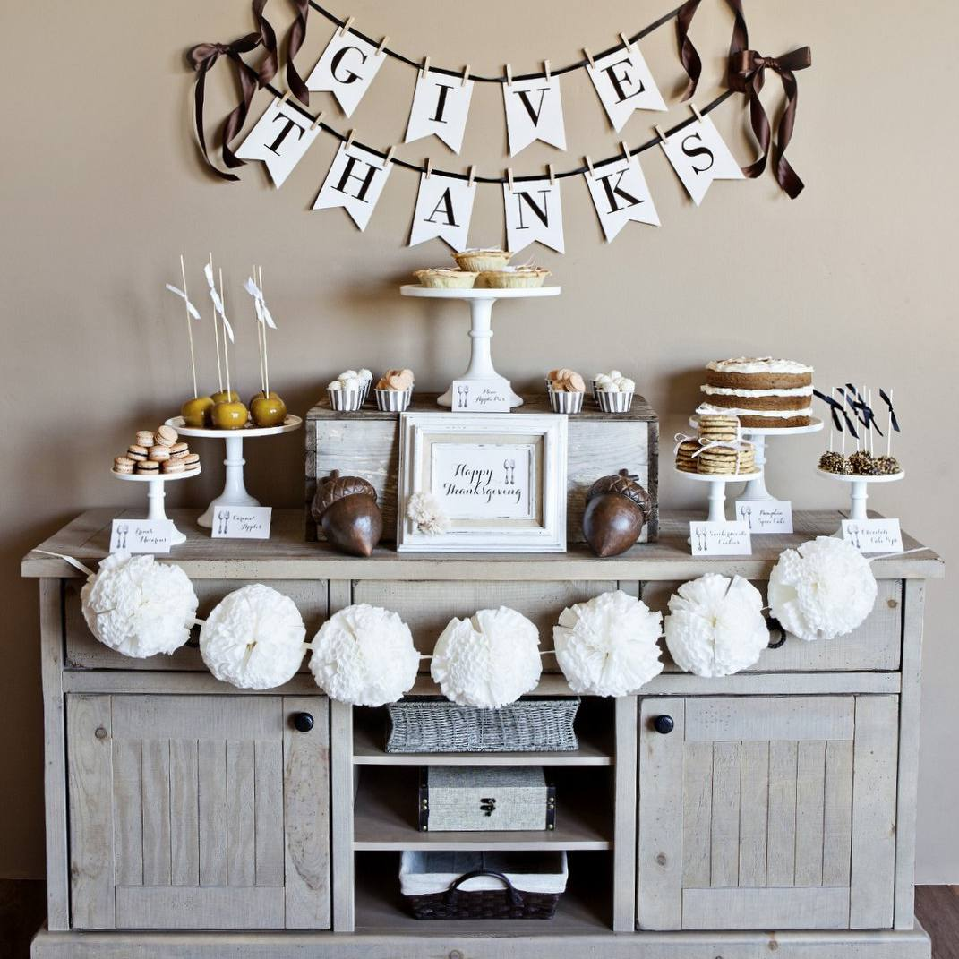 A buffet decorated with white and brown Thanksgiving decorations.