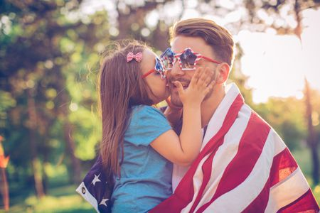 Father And Daughter Outdoors In A Meadow On July 4th