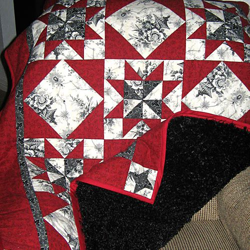 Red quilt with black backing on a couch.