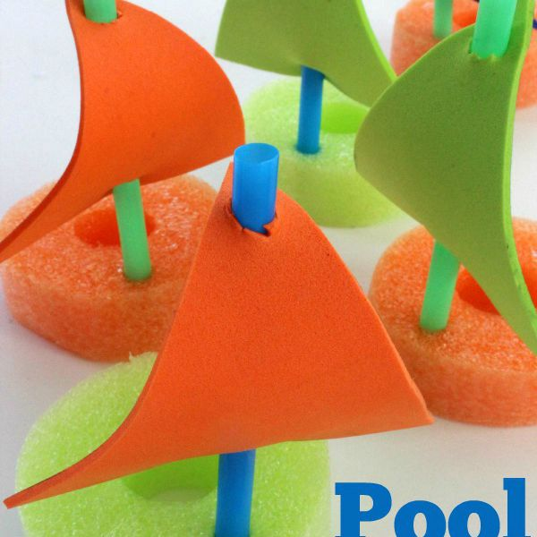 Pool noodle boats with green and orange bases and green and orange sails connected with glue and green straws.