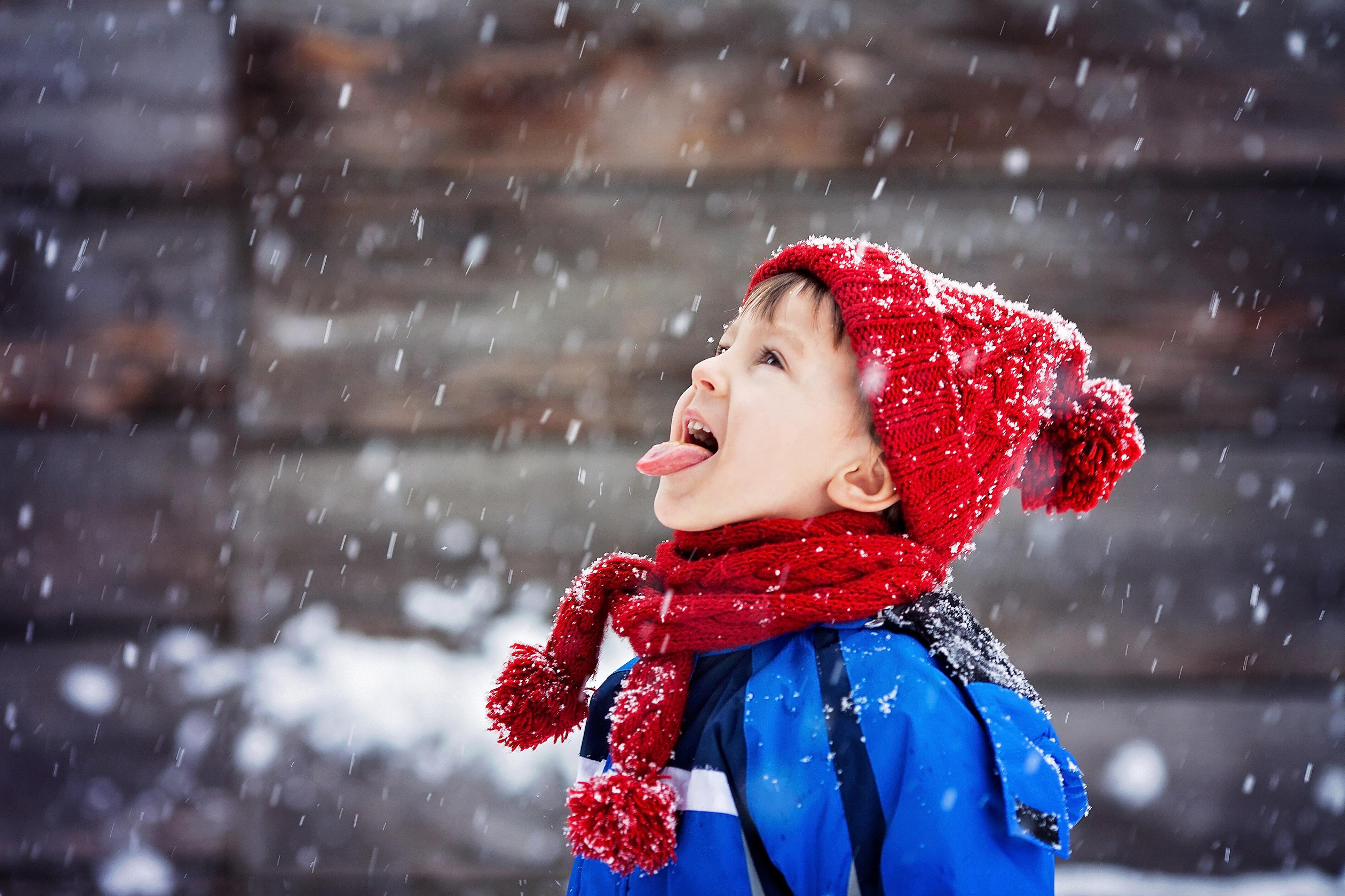 Close portrait of little boy, catching snowflakes