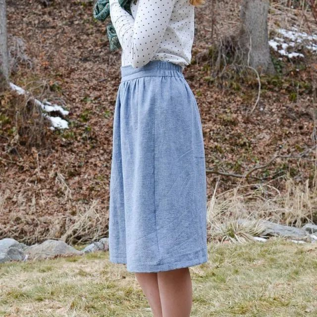 A woman wearing a blue skirt, standing outside