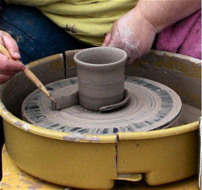 Trimming the pot on the pottery wheel