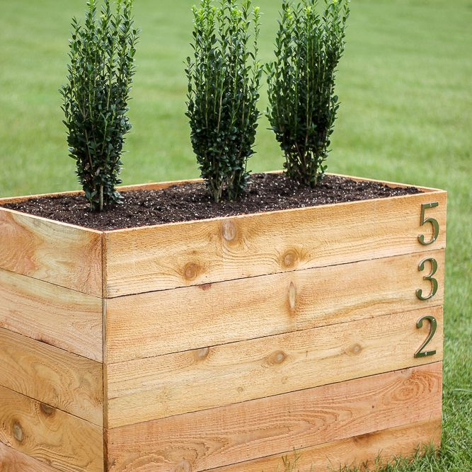 A large cedar planter box with address numbers