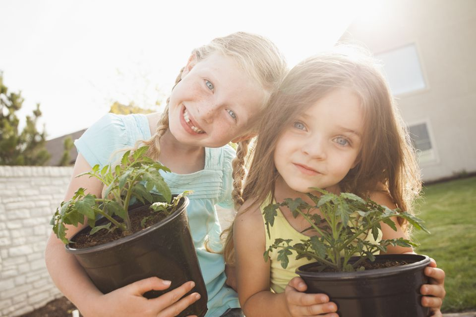 Two girls holding potted plants.
